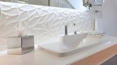 Design, cette salle de bains blanche avec baignoire, miroir rétroéclairé, faience matiérée et lavabo Bouroullec de l'hôtel Chavanel à Paris