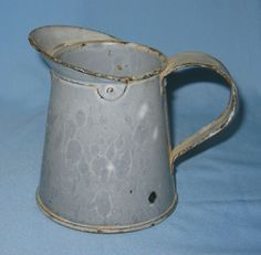 Vintage gray graniteware enamelware creamer or syrup pitcher with riveted spout and handle.