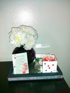Here's what I decided to do with some of the $5 Goodwill finds..I painted the white picture frame and added a mirror and some bling and turned it into a tray..added the $3 carnations from Walmart in to the dollar vase and a dollar candle from Walmart in the Nate Berkus candle holder