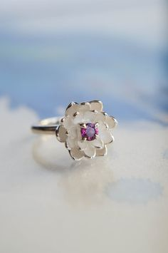Lotus flower proposal ring is hand-sculpted from silver sheet, it features several layers of petals and adorned with beautiful pink rhodolite garnet (or another gemstone by your choice). Edges of this engagement ring are polished, but flower inside has white matte color. This lotus jewelry piece will perfectly look as promise ring, engagement ring and will be great for everyday wear or any special occasion as well. She will appreciate this unique gift for her!  Diameter of flower: 13-15 mm…