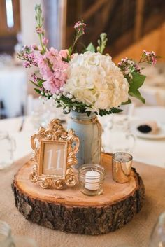 Wedding reception center piece on a wood slab with gold frame for table number and white hydrangeas