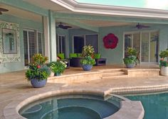 This spacious patio features neutral Terrazzo tiles that lead the way to a relaxing pool and hot tub area. Blue stucco covers the home exterior, while a covered sitting area with a brown wicker furniture set offers a comfortable place for kicking back and enjoying the shade.