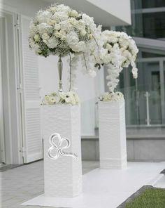 Imponenti ma minimali vasi d'argento ricolmi di una composizione floreale morbida e leggera da far invidia ad una nuvola, attendono l'uscita della sposa