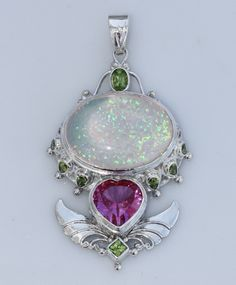 The Mermaid Goddess pendant is an amazing design by Shankari the Alchemist featuring a large oval White Opal Triplet surrounded by Peridot gemstones above a large Pink Topaz Heart. The White Opal Triplet provides Victory over Past Pain while the Peridot gemstones are for Healing, Wisdom and Cleansing. The Pink Topaz gemstone will help you understand your heart's deepest desire and boost your sense of Humor and fantasy. The handmade Sterling Silver Wings of Freedom will help you access your…