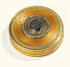 A CIRCULAR TWO-COLOUR GOLD AND ENAMEL SNUFF BOX, AUGUSTE-GASPARD TURMINE, PARIS, 1784 the lid with a central glass cameo carved with a satyr's mask within coloured enamel foliage in chased ropework framed by rose diamonds, the  deep yellow translucent enamel ground with applied corded rims chased in two-coloured gold, maker's mark, charge and décharge of Henri Clavel, Paris date letter