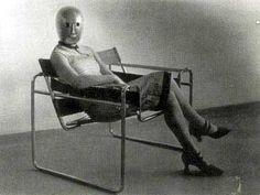 Mujer con máscara de Schlemmer sentada en la Silla Wassily de Marcel Breuer (1927)