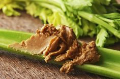 Natural chunky peanut butter on celery, close-up