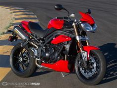 Here is one of the 2011 Triumph Speed Triple 1050 with a load of accessories slathered all over it. Arrow exhaust, belly pan, fly screen and a few anodized bits make this bike even more attractive. Go ahead, touch her, she won't sue.