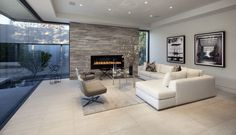 This ultra-modern family room pairs a white L-shaped contemporary sectional with a pair of grey accent chairs around a minimalist glass and metal coffee table. Gas fireplace stands wrapped in a large grey brick wall, surrounded by floor to ceiling glass on the exterior.