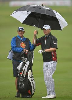 Michael Hoey of Northern Ireland and caddie ponder during the weather delayed first round of The Nelson Mandela Championship at Mount Edgecombe Country Club on December 12, 2013 in Durban, South Africa.