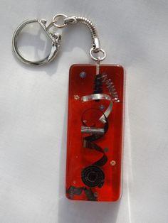Porte-clés métal et résine sur fond rouge