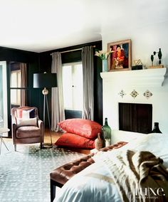 A rug from Empiric grounds the master bedroom, where White painted the walls a…