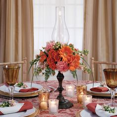 Modern Orange Centerpiece with taper candles and hurricane vases atop daises and roses