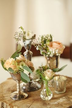 Roses, ranunculus, seeded eucalyptus, waxflower, jasmine, and scabiosa pods arranged in mix-and-match silver compotes and candlesticks. Photo by j.woodbery photography