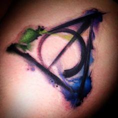 Deathly Hallows tattoo by Chris Toler. #HarryPotter #DeathlyHallows #watercolortattoo #tattooart #perfecttattoo