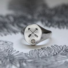 chunky silver signet ring engraved with crossed arrows and champagne diamond