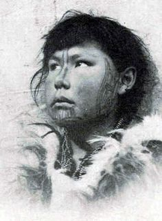 Young Inuit girl with facial tattoos. Black and white. Photographer unknown. ~ 1900. They thought that a not tattoed woman could not  find peace after death. A seasoned woman was using a needle under the skin followed by lampblack coated wire. These designs are not only proof of endurance and resistance to pain, they also aim to attract animals that will bring wealth to the family.  http://www.vanishingtattoo.com/arctic_tattoos.htm