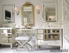 Mirrored Master Bath  Like a powder room in a 1920s grand hotel, this vintage-style bathroom by designer Carrie Hayden features a vanity table surrounded by mirrored bureaus fitted with sinks. Thick slabs of honed Calacatta marble for backsplashes and counters, along with Waterworks Opus faucets and an antique gilt mirror, complete the dressy, old-world European feeling.