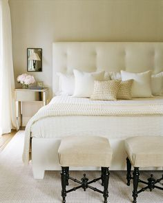 warm neutral bedroom with upholstered headboard and nightstand with fresh flowers