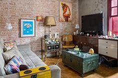 Casa pequena, casa charmosa, detalhes da decoração da sala de estar com parede de tijolinhos, sofá cinza, quadros.