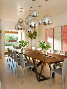 Grey leather Linda dining chairs provide sleek contrast to the organic wood table.  The fun, silver, orb pendants are great as a chandelier.