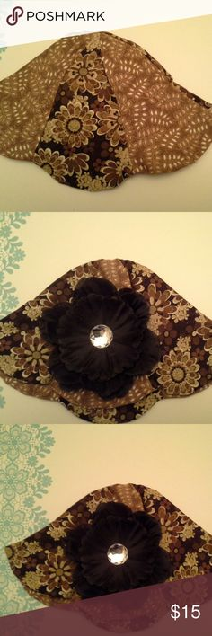 This is a beautiful tulip hat in shades of browns. This hat if for a 6 month old baby.  It has a black flower attached to it. handmade Accessories Hats