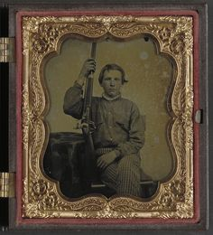 Holding his rifle, a very young, Private William H. Presgraves of Company K, 97th Militia Virginia Infantry Regiment.