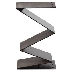 """Zigzagging into geometric form, the Arteriors Zippe side table strikes a sculptural pose. Embossed shagreen lends designer Barry Dixon's intoxicating piece bold texture. 16""""W x 12""""D x 26""""H; Matte black iron"""