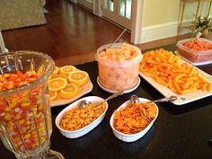 orange snacks laid out over a black tablecloth - love how easy this would be