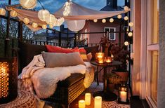 A cosy balcony with lit LED lighting chains, a canopy, lanterns with lit candles and a sofa filled with cushions and sheepskin rugs.
