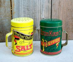 Bright graphics make these vintage salt and pepper shakers a visual delight in your kitchen or collection. The typography is reminiscent of a saloon in the wild west...I can hear the piano now! Good vintage condition, the pepper shaker shows no signs of rust. The salt shaker has minor rust on the inside of the lid, a bit on the rim of the handle, and some corrosion inside where the handle attaches to the body, whichis barely visible from an outside view at arms-length. Dimensions: 3 tall, 2…