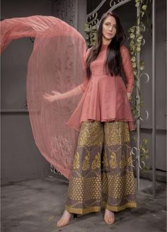 An eye catching, traditional silhouette with a hand embroidery stitched pattern is made to perfection to make every event a GRAND occasion. The peach organza short peplum shirt paired with block printing rust Indian raw silk bell bottom encapsulates Pakistani Fashion Casual, Pakistani Dresses Casual, Pakistani Dress Design, Indian Fashion, Pakistani Mehndi Dress, Pakistani Party Wear, Indian Party Wear, Kurta Designs, Kurti Designs Party Wear