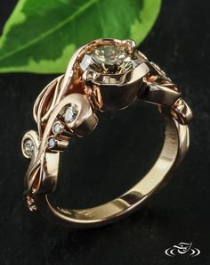 Rose Gold Verdure and Champagne Diamond Engagement RingPierced organic verdure style engagement ring cast in rose gold holds in a wrap setting a sparkling champagne diamond. Bezel set round diamonds nestle among the cast leaves and curls.#Ido #GreenLakeMade #EngagementRing