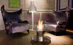 WELLBEING Tavolino realizzato in acciaio lucido con lavorazione laser. Di forte impatto emotivo assolve due funzioni: calore e tavolino portaoggetti. Fornito di protezione in vetro pirex.
