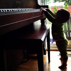 Baby discovering a piano!.... we need a piano in our house.. i can start playing again. they can learn. perfect.