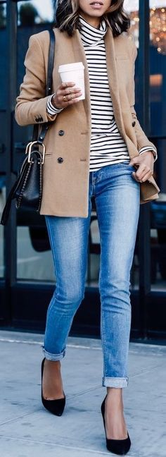 Camel jacket over striped top and blue jeans.