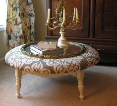 Looks  like old round table cut down, painted and then padding and fabric added on top to make a coffee table.  Can't find the source, but looks like a cute idea.