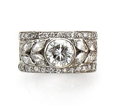 A diamond ring the wide openwork band centering a round brilliant-cut diamond…