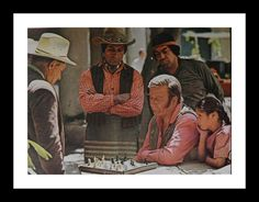"""Duke John Wayne playing chess on set, """"The Undefeated"""".  Stoic actor mesmerized by next move.  1969."""