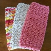 Back and Forth Dishcloth pattern worked up in a coral color, off-white, and a variegated orange, white, yellow yarn.