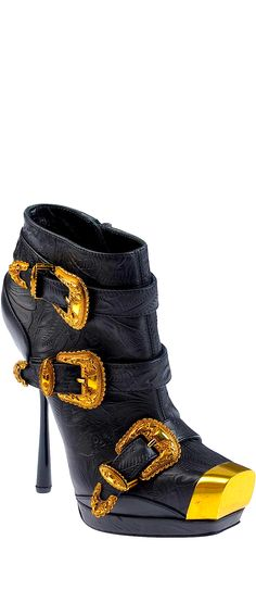 Black booties, shiny gold buckles and toe tip. Short black boots. Ankle high boots with spike heel. Alexander McQueen