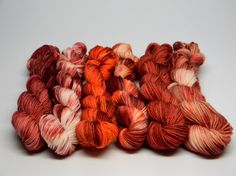 Daylily - Set of Six Jig Monkey Mini Skeins - 20g/93 yards each - 120g/558 yards total August. Bright sun, brighter colors. Orange, red, rust, salmon, pink, peach, cream, white. Daylilies bloom in the heat and retire in the evenings. These colors will make an impression both day and night. Jig Monkey Yarn Base - 75% Superwash Merino/25% Nylon 20g/93 yards/mini skein Soft, elastic and durable; a gorgeous sock yarn. Hand Wash ~ Air Dry Want to add a little stripe to your project? Working a…