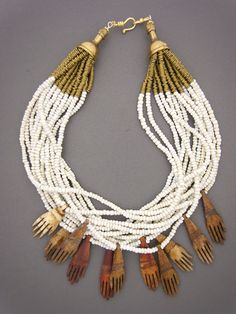 We often see stylized hand pendants, which symbolize protection for the wearer. But these carved bone hands from Africa are more realistic. Actually, an unusual find. With 15 strands of old white glass African beads, brass heishi from Kenya, bronze cones, and a gold-filled hook and eye clasp
