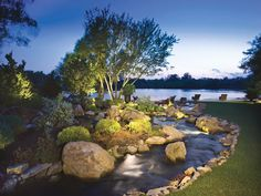 22 Landscape Lighting Ideas: This scene is lit with the entire view in mind, not just the water feature. Uplit trees across the viewing area provide balance; the designer used more lumen intensity and a wider lamp spread on the tree in the middle, which is the focal point. A bonus tip for lighting evergreens: using a blue lens intensifies their green color. From DIYnetwork.com