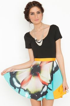 I like the look! Short circle skirt, black scoop neck tee, geometric necklace and braided hair.
