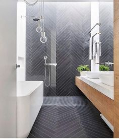 #Repost @bathrooms_of_insta (@get_repost)  Beautiful Black Herringbone Tiles!  @bookofinteriors via @purewalldesign #herringbone #herringbonetile #blacktiles #tileshower #bathtub #woodvanity