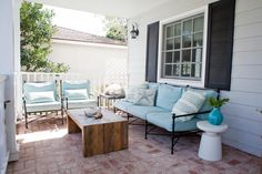 Aqua blue outdoor cushions on black metal chairs and a sofa bring a beachy feel to this front porch. A chunky wooden coffee table balances the chairs' and sofa's slim silhouettes.