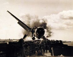 USS Enterprise (CV 6). Crash landing of F6F #30, piloted by Ensign Bryon M. Johnson on the flight deck while enroute to attack Makin Island in the Gilbert Islands. Lieutenant Walter L. Chewning, USNR, catapult officer, clambering up the side of the plane to assist pilot Ensign Johnson, from the flaming cockpit. Johnson escaped with little personal damage. Photograph released November 10, 1943. Official U.S. Navy photograph, now in the collections of the National Archives.