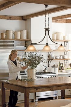 cast iron large three pendant lighting fixture above a kitchen table ...