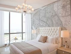 Tufted headboard, mapped wall, and gorgeous light fixture